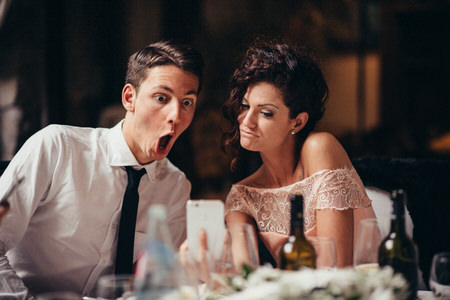 A wedding guest who is amazed by looking at a photograph on a friend's smartphone